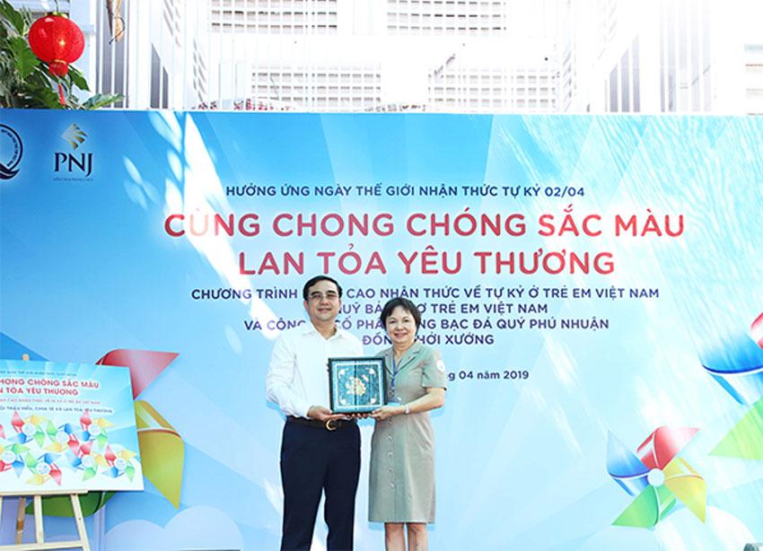 Bà Cao Thị Ngọc Dung trao, đại diện PNJ trao tặng quà lưu niệm cho đại diện Trung Tâm phục hồi chức năng và trợ giúp trẻ khuyết tật – ông Nguyễn Xuân Thắng (Giám đốc trung tâm)